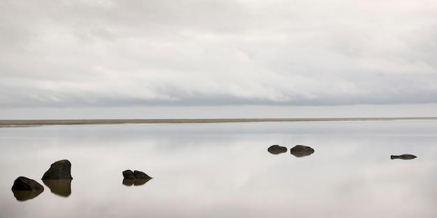 Ciel nuageux, reflété dans une eau calme, avec des roches brisant la surface de l'océan