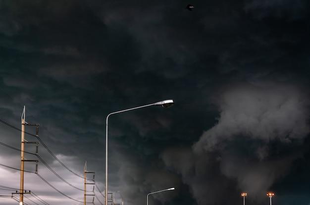 Ciel orageux avec lampadaire et pylônes électriques triphasés.