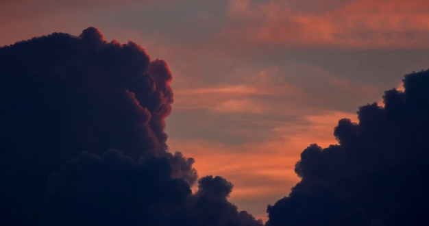 Ciel orange dramatique entre des nuages sombres et épais qui sont illuminés par le coucher de soleil rouge et cachés derrière les nuages.