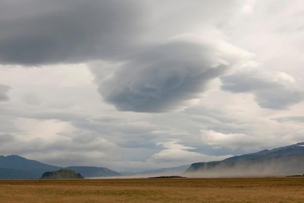 Ciel sombre et terres agricoles avec paysage de montagne