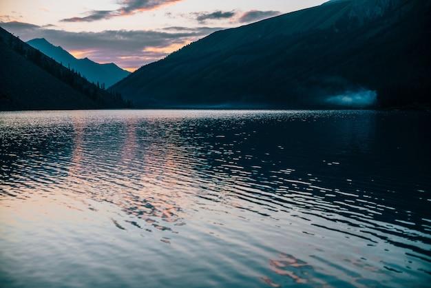 Le ciel vif du lever du soleil se reflète dans le lac alpin pur près des silhouettes de montagne. paysage coloré avec de l'eau calme du lac de montagne aux couleurs de l'aube. beau paysage avec ondulation de l'eau en matinée ensoleillée.