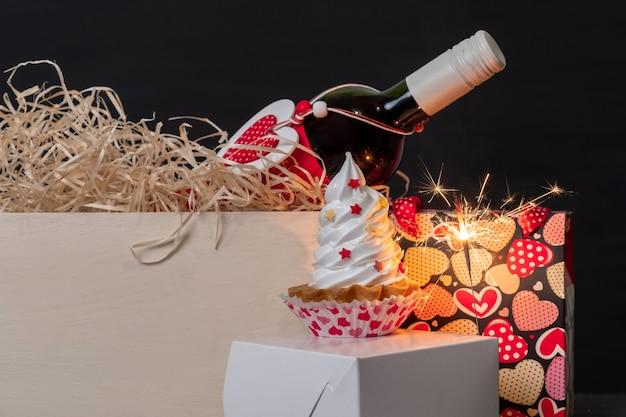 Cierge magique, bouteille de vin, sac à provisions avec coeurs et gâteau meringué sur fond noir pour la saint-valentin.