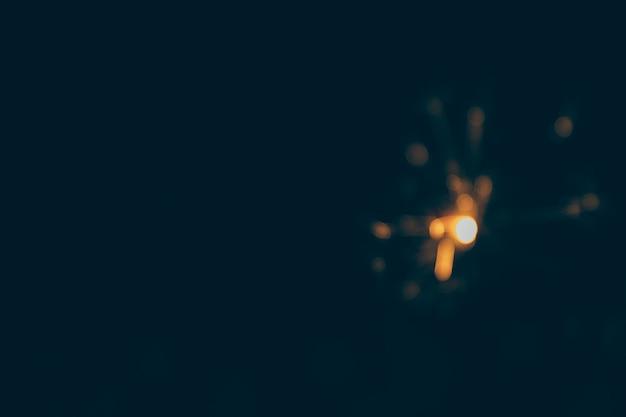 Cierge magique illuminé sur un fond noir flou