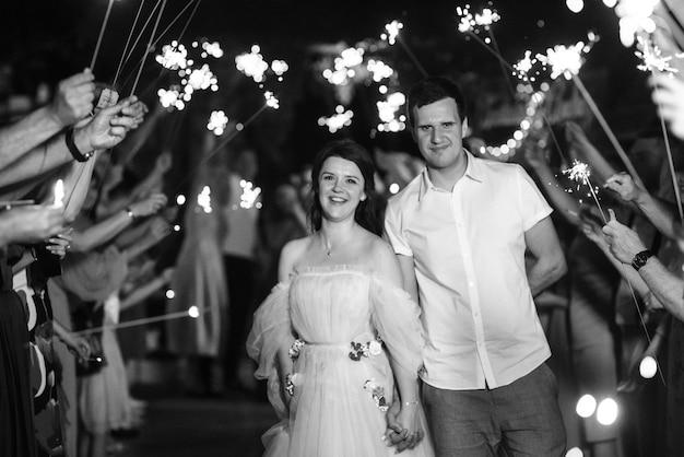Des Cierges Magiques Au Mariage Des Jeunes Mariés Entre Les Mains D'invités Joyeux Photo Premium