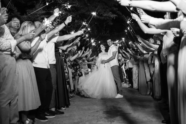 Des cierges magiques au mariage des jeunes mariés entre les mains d'invités joyeux