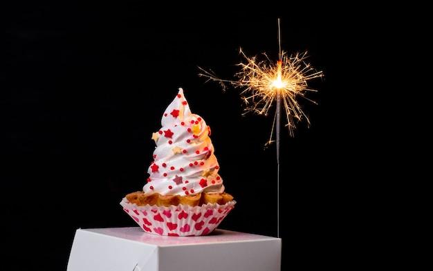Cierges magiques et gâteau de meringue sur le fond noir pour la saint-valentin.