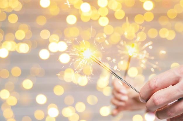 Cierges magiques de noël entre les mains d'un homme et d'une femme, vacances, mise au point sélective.