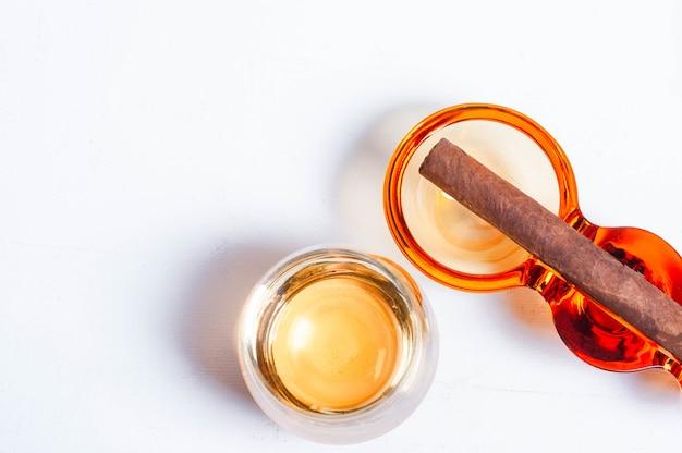 Cigare, cendrier, ciseaux à cigarettes, table en béton blanc, verre à whisky plus léger.