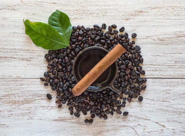 Cigare sur une tasse de café noir avec des grains de café.