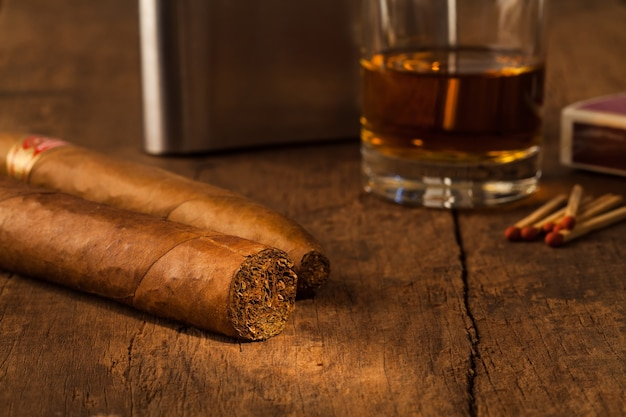 Cigare sur une vieille table en bois avec le meilleur whisky
