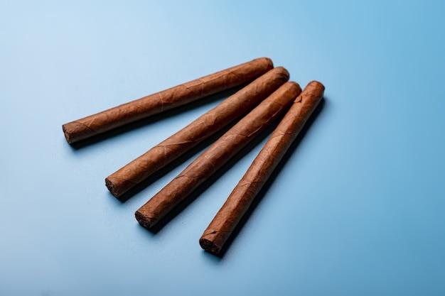 Cigares cubains faits à la main sur fond bleu.