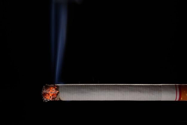 Cigarette allumée et brûlante avec de la fumée sur fond noir