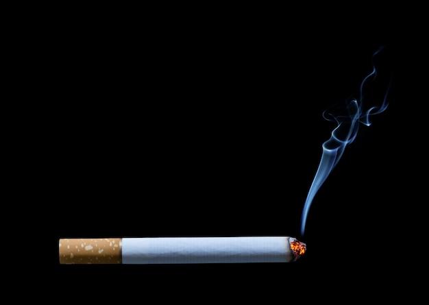 Cigarette allumée isolée sur fond noir