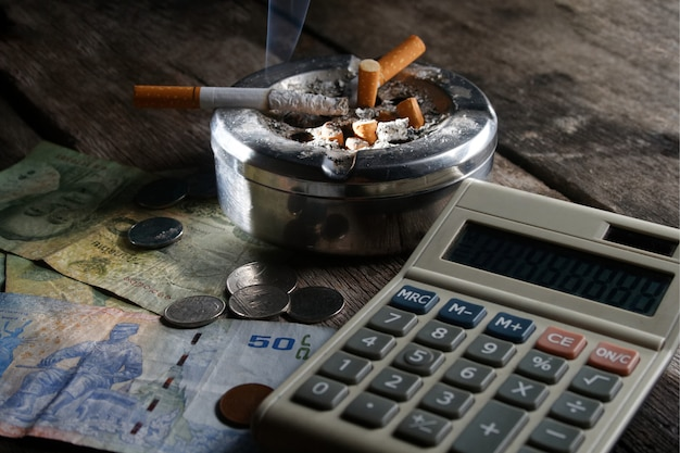 Cigarette et calculatrice avec de l'argent