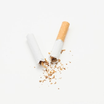 Cigarette cassée et tabac sur isolé sur fond blanc