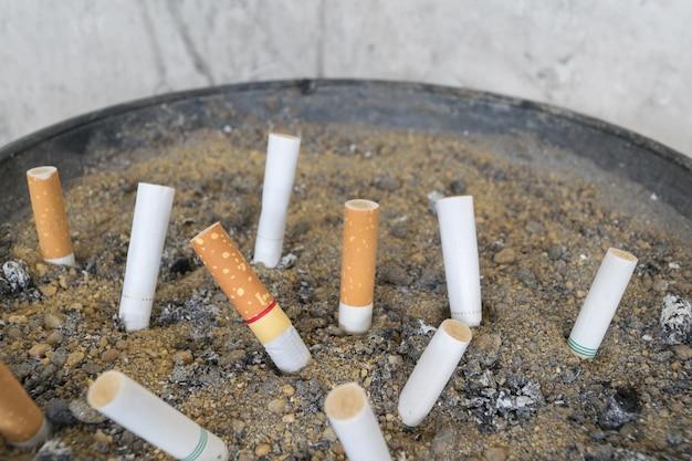 Cigarette dans un cendrier extérieur avec du sable closeup