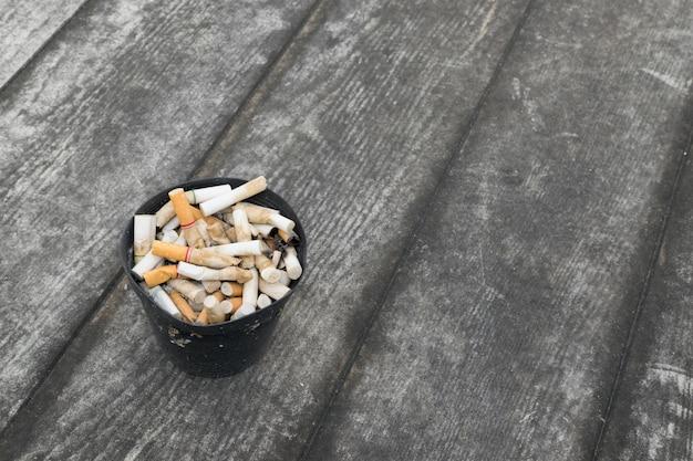 Cigarette dans un cendrier extérieur avec du sable sur le plancher en bois