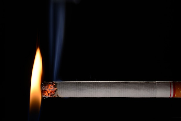 Cigarette éclairée par une petite flamme sur fond noir