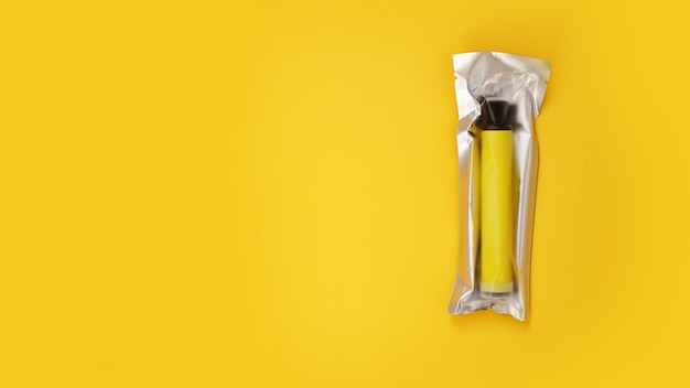 Cigarette électronique jetable jaune en emballage sur mur jaune
