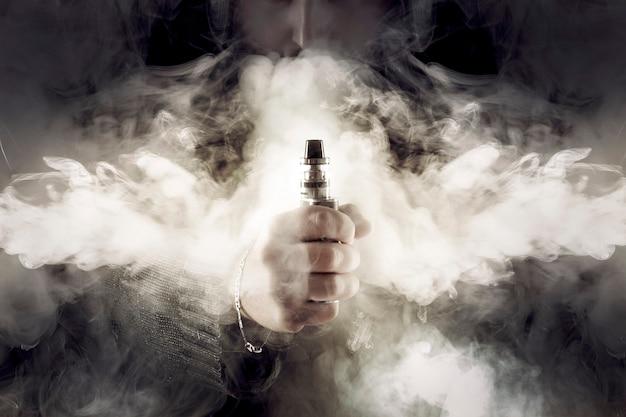 Cigarette électronique à la main au milieu d'une épaisse fumée