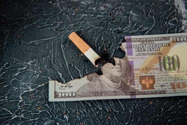 Cigarette fumante et dollar sur table grise