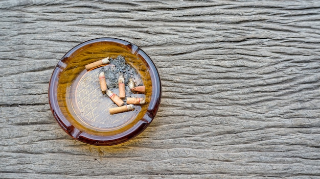 Cigarettes et cendrier sur un fond en bois.