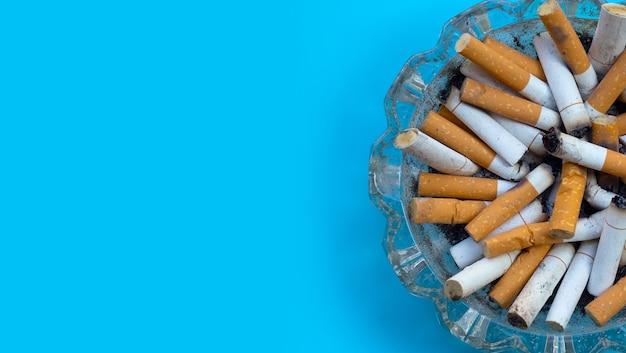 Cigarettes fumées sur surface bleue