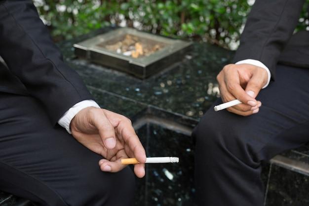 Cigarettes d'hommes d'affaires pour fumer assis dans le parc