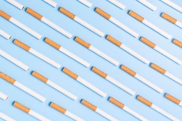 Cigarettes à jeter à plat sur fond bleu