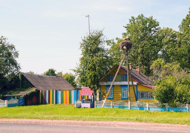 Les cigognes sont assises dans un nid sur un lampadaire près d'une maison colorée avec un puits.