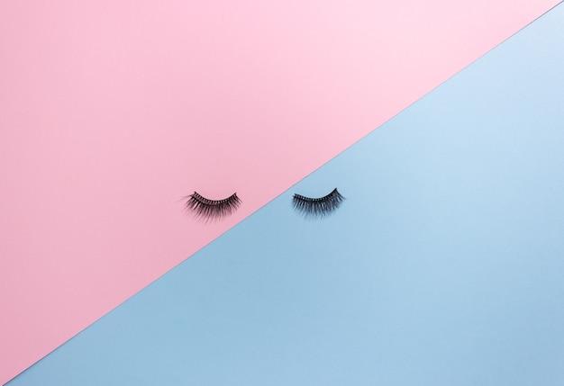 Cils artificiels sur fond rose-bleu, vue de dessus. cils pour le maquillage, extensions de cils