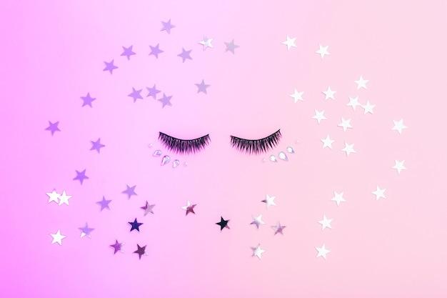 Cils artificiels pour le maquillage et les étoiles sur un fond coloré