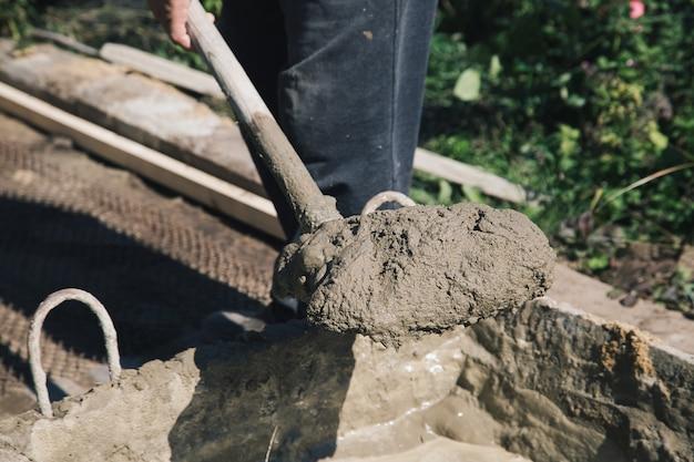 Ciment des allées de jardin sur un treillis métallique, travaux de construction dans le jardin.