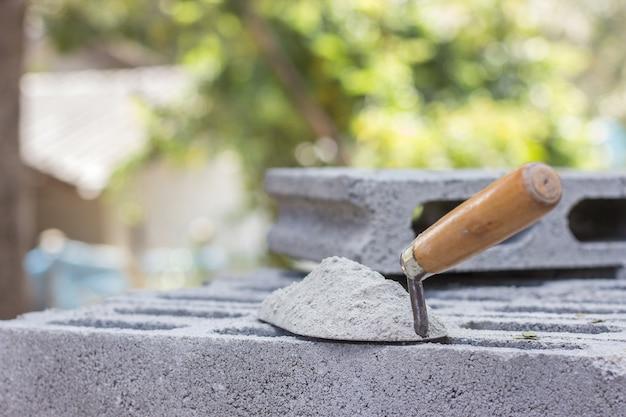 Ciment en poudre avec une truelle posée sur la brique pour les travaux de construction