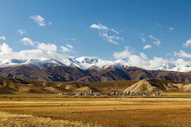 Cimetière au kirghizistan au pied des montagnes enneigées