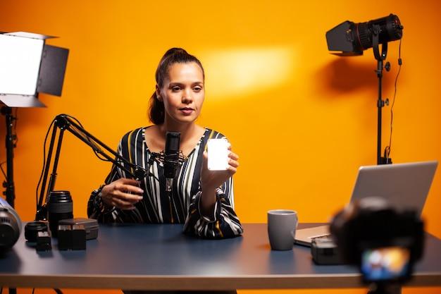 Cinéaste montrant une mini lumière led lors de l'enregistrement d'un podcast