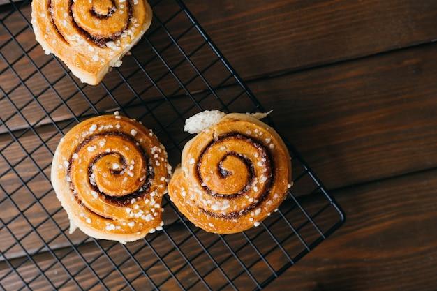 Cinnabons a gagné une grille sur la table. concept alimentaire. pâtisseries sucrées faites maison sur un fond en bois. vue de dessus