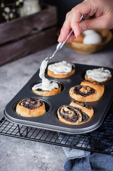 Cinnamon rouler avec des graines de pavot sur fond. pain à la cannelle fait maison avec crème au fromage à la crème
