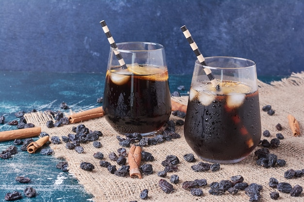 Cinnamonnd sultana avec une tasse de boisson sur bleu.