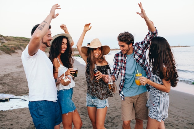 Cinq amis célébrant à la plage