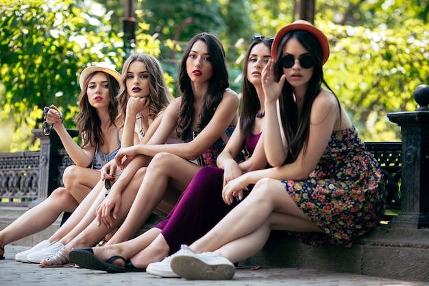 Cinq belles jeunes femmes posant dans le parc