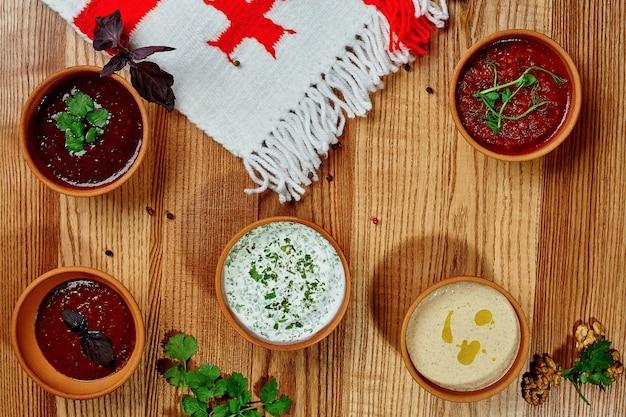 Cinq bols en argile avec des sauces géorgiennes traditionnelles