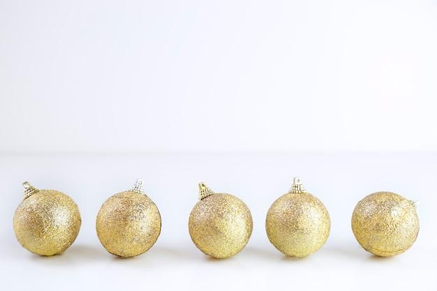 Cinq boules de noël dorées sur fond blanc. espace de copie.