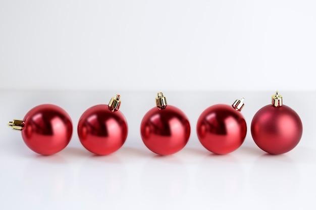 Cinq boules de noël rouges sur fond blanc. espace de copie.