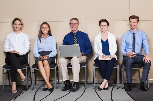 Cinq candidats souriant assis dans la salle d'attente
