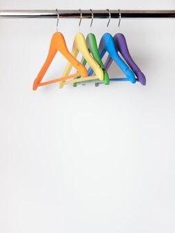 Cinq cintres vides multicolores suspendus dans une armoire