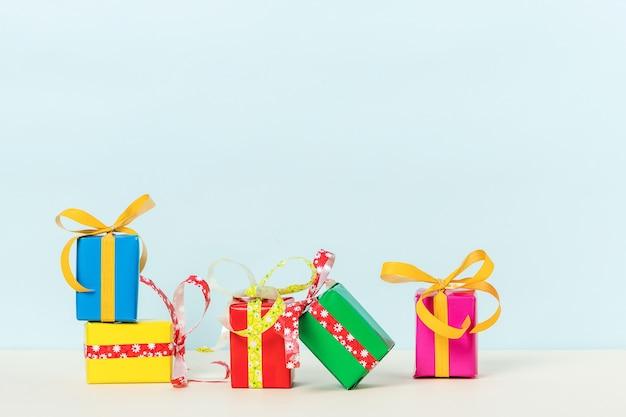 Cinq coffrets cadeaux colorés sur fond pastel.