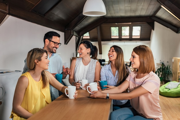 Cinq collègues en train de rire pendant la pause dans un espace de coworking moderne.