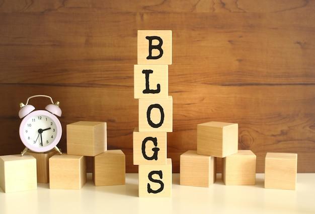 Cinq cubes en bois empilés verticalement pour former le mot blogs sur fond marron. des cubes sont dispersés à proximité et il y a une horloge. concepts de vue de face