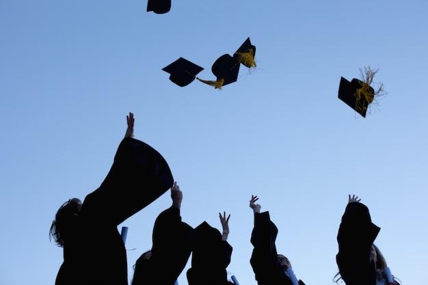 Cinq diplômés jetant leurs chapeaux dans le ciel